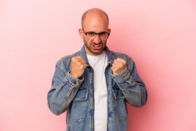 Junger kaukasischer glatzköpfiger mann, der auf rosafarbenem hintergrund isoliert ist, verärgert schreiend mit angespannten händen.