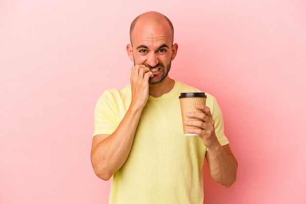 Junger kaukasischer glatzköpfiger mann, der einen kaffee zum mitnehmen hält, einzeln auf rosafarbenem hintergrund, der fingernägel beißt, nervös und sehr ängstlich.