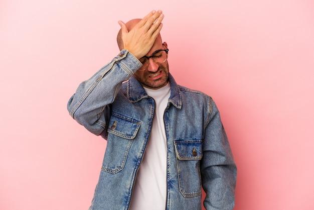 Junger kaukasischer glatzköpfiger mann einzeln auf rosafarbenem hintergrund, der etwas vergisst, mit der handfläche auf die stirn schlägt und die augen schließt.
