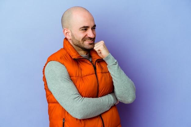 Junger kaukasischer glatzköpfiger mann isoliert auf lila hintergrund, der glücklich und selbstbewusst lächelt und das kinn mit der hand berührt
