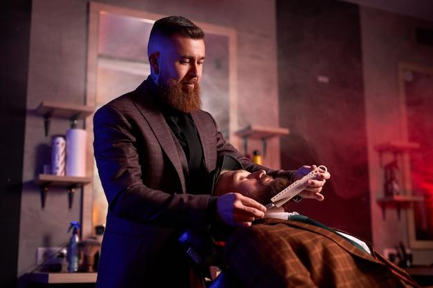 Junger kaukasischer gutaussehender mann auf stuhl des friseurs, der verfahren des rasierens hat