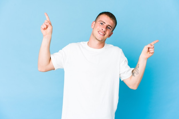 Junger kaukasischer gutaussehender mann, der auf verschiedene kopienräume zeigt, einen von ihnen wählend, mit dem finger zeigend.