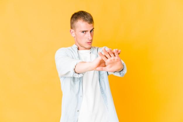 Junger kaukasischer gutaussehender mann, der mit ausgestreckter hand steht, die stoppschild zeigt, das sie verhindert.