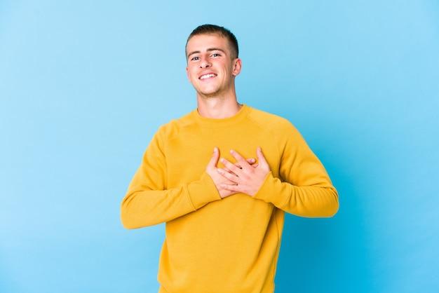 Junger kaukasischer gutaussehender mann hat freundlichen ausdruck und drückt handfläche zur brust. liebeskonzept.
