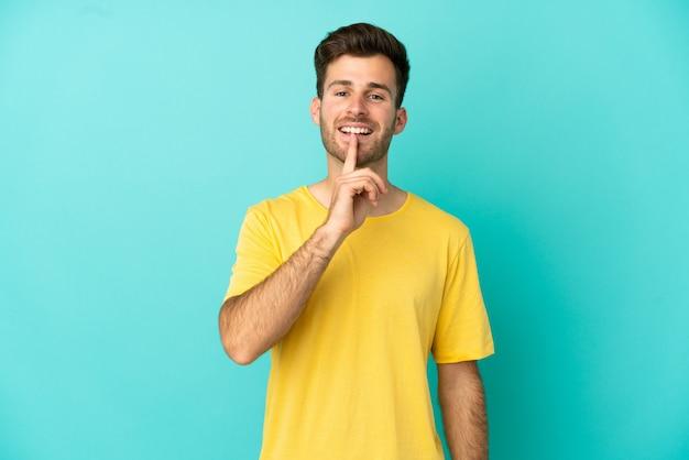 Junger kaukasischer gutaussehender mann isoliert auf blauem hintergrund, der ein zeichen der stille zeigt, geste, die finger in den mund steckt