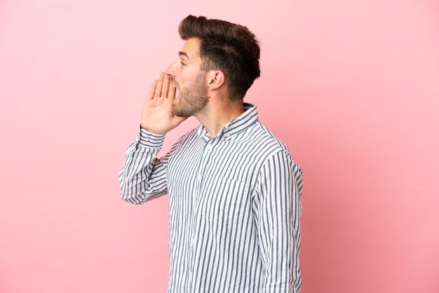 Junger kaukasischer gutaussehender mann isoliert auf rosa hintergrund, der mit weit geöffnetem mund zur seite schreit
