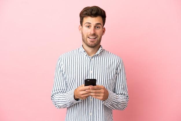 Junger kaukasischer gutaussehender mann isoliert auf rosa hintergrund überrascht und sendet eine nachricht