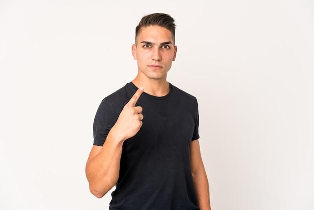 Junger kaukasischer gutaussehender mann isoliert, der mit dem finger auf sie zeigt, als ob die einladung näher kommt.
