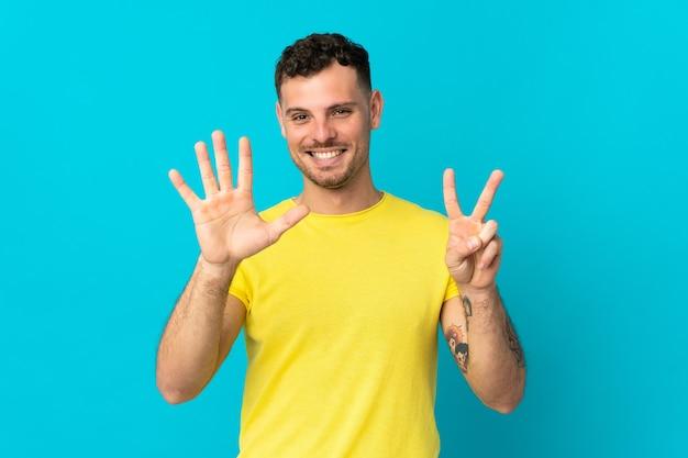 Junger kaukasischer gutaussehender mann lokalisiert auf blau, das sieben mit den fingern zählt