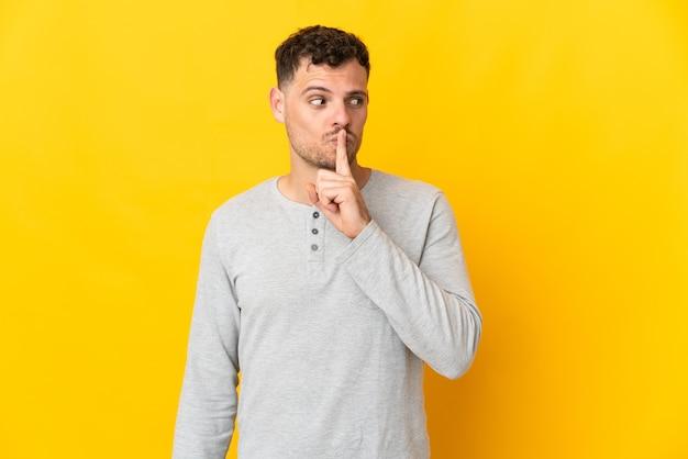 Junger kaukasischer gutaussehender mann lokalisiert auf gelb, der ein zeichen der stille geste zeigt finger in den mund setzt