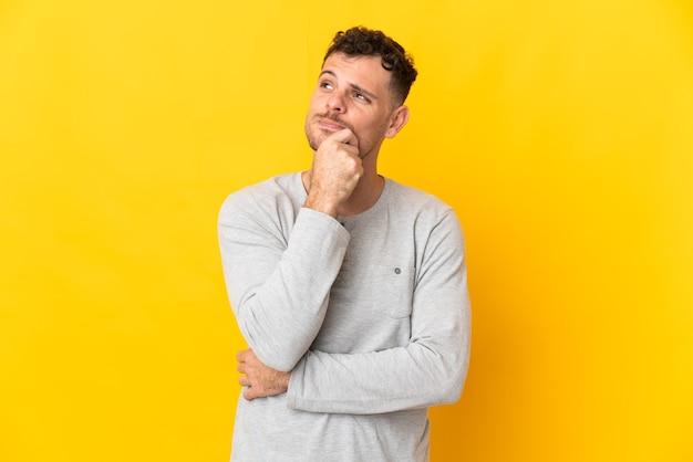 Junger kaukasischer gutaussehender mann lokalisiert auf gelber wand, die eine idee beim nachschlagen denkt