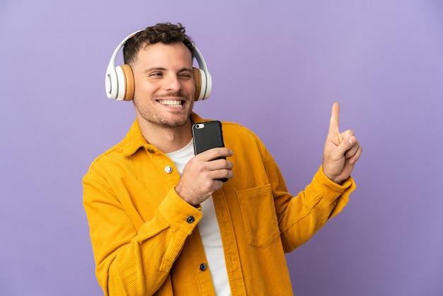 Junger kaukasischer gutaussehender mann lokalisiert auf lila hörende musik mit einem handy und gesang