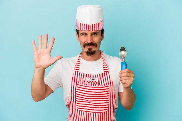 Junger kaukasischer hersteller, der eine schaufel auf blauem hintergrund isoliert hält, lächelt fröhlich und zeigt nummer fünf mit den fingern.