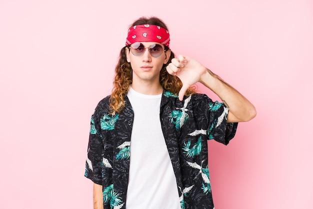 Junger kaukasischer hippie-mann isoliert, der eine abneigungsgeste zeigt, daumen nach unten. uneinigkeit konzept.