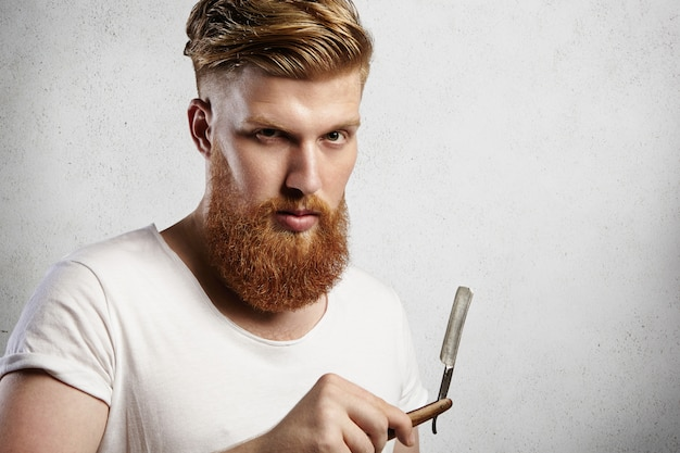 Junger kaukasischer hipster-ähnlicher mann im weißen t-shirt, der versucht zu entscheiden, ob er seinen langen bart mit den roten haaren rasiert oder nicht. stilvoller kerl, der gerade rasiermesser mit ernstem gesichtsausdruck und blick hält.