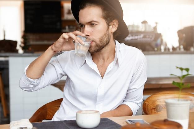 Junger kaukasischer hipster gekleidet im weißen hemd, das wasser aus glas während der kaffeepause in der cafeteria trinkt. stilvoller bärtiger mann im schwarzen hut, der allein im modernen café-innenraum entspannt. horizontal