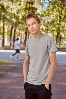 Junger kaukasischer hübscher mann steht im öffentlichen park.