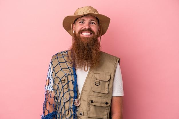 Junger kaukasischer ingwerfischer mit langem bart, der ein auf rosafarbenem hintergrund isoliertes netz hält