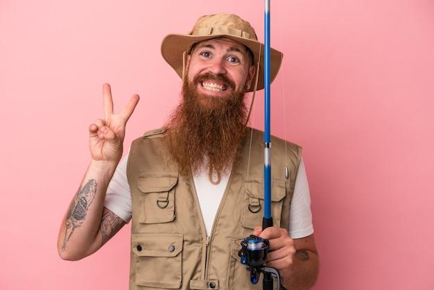 Junger kaukasischer ingwerfischer mit langem bart, der eine stange einzeln auf rosafarbenem hintergrund hält, freudig und sorglos, die ein friedenssymbol mit den fingern zeigt.