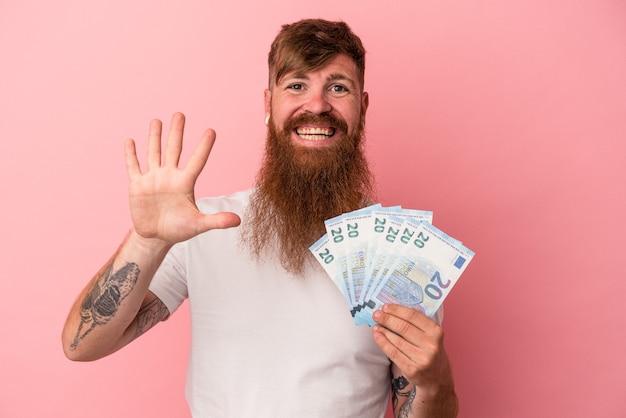 Junger kaukasischer ingwermann mit langem bart, der banknoten einzeln auf rosafarbenem hintergrund hält, lächelt fröhlich und zeigt nummer fünf mit den fingern.