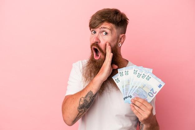 Junger kaukasischer ingwermann mit langem bart, der banknoten einzeln auf rosafarbenem hintergrund hält, sagt eine geheime heiße bremsnachricht und schaut beiseite