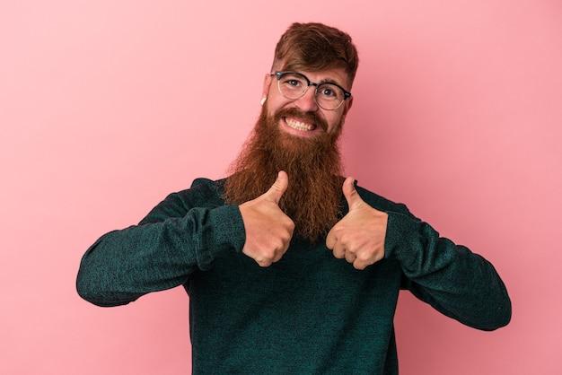 Junger kaukasischer ingwermann mit langem bart einzeln auf rosafarbenem hintergrund, der beide daumen hochhebt, lächelt und selbstbewusst.
