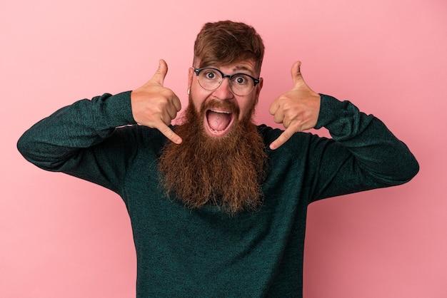 Junger kaukasischer ingwermann mit langem bart einzeln auf rosafarbenem hintergrund, der eine handy-anrufgeste mit den fingern zeigt.