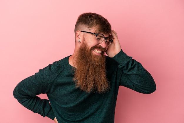 Junger kaukasischer ingwermann mit langem bart einzeln auf rosafarbenem hintergrund, der viel lacht. glück-konzept.