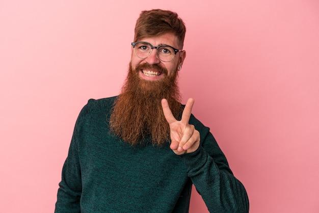 Junger kaukasischer ingwermann mit langem bart einzeln auf rosafarbenem hintergrund, fröhlich und sorglos, der ein friedenssymbol mit den fingern zeigt.