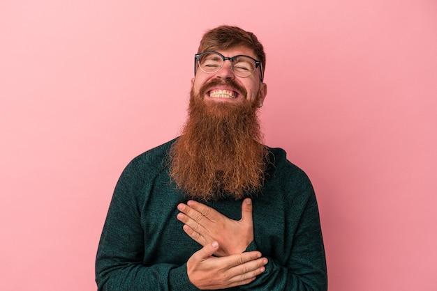 Junger kaukasischer ingwermann mit langem bart einzeln auf rosafarbenem hintergrund lacht laut und hält die hand auf der brust.