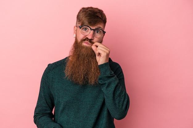 Junger kaukasischer ingwermann mit langem bart einzeln auf rosafarbenem hintergrund mit fingern auf den lippen, die ein geheimnis bewahren.