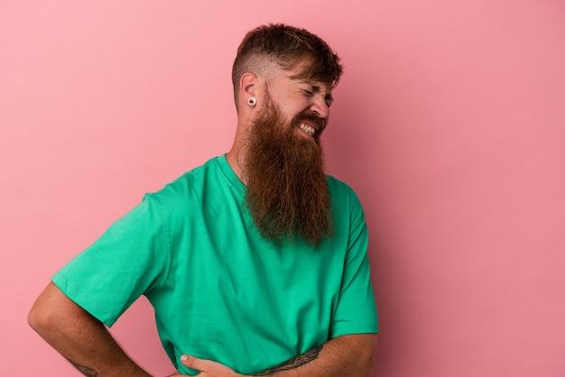 Junger kaukasischer ingwermann mit langem bart einzeln auf rosafarbenem hintergrund mit leberschmerzen, bauchschmerzen.
