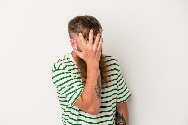 Junger kaukasischer ingwermann mit langem bart isoliert auf weißem hintergrund blinzelt erschrocken und nervös durch die finger.