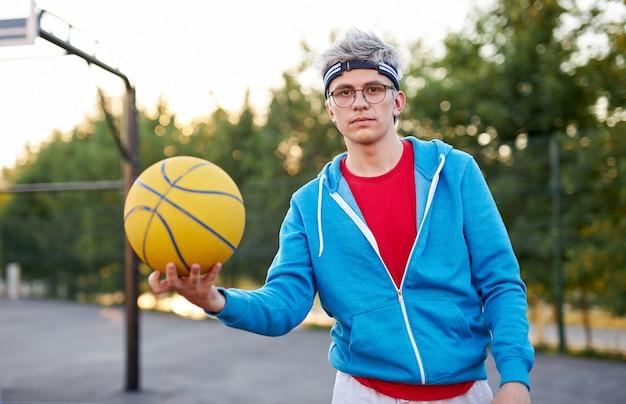 Junger kaukasischer jugendlich junge, der basketball spielt