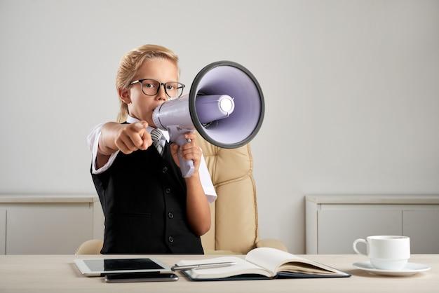 Junger kaukasischer junge, der am exekutivschreibtisch im büro mit lautsprecher steht und finger zeigt