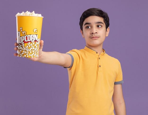 Junger kaukasischer junge, der einen eimer popcorn ausstreckt und auf die seite schaut, die auf lila wand isoliert ist?