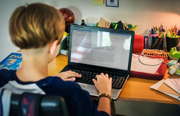 Junger kaukasischer junge, der hausarbeit mit computerlaptop tut