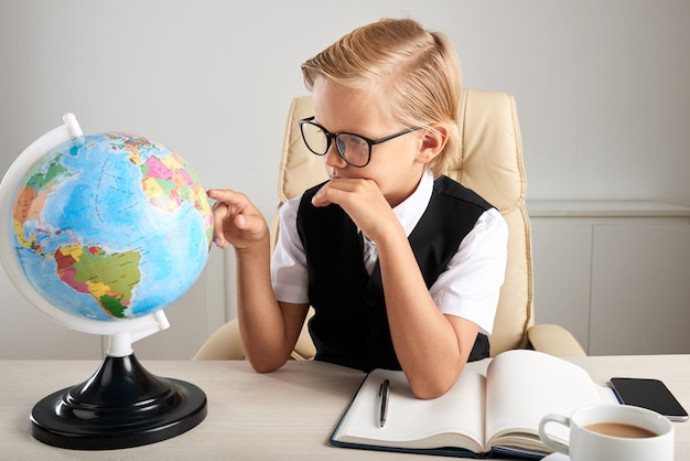 Junger kaukasischer junge, der im exekutivstuhl im büro sitzt und erdkugel betrachtet