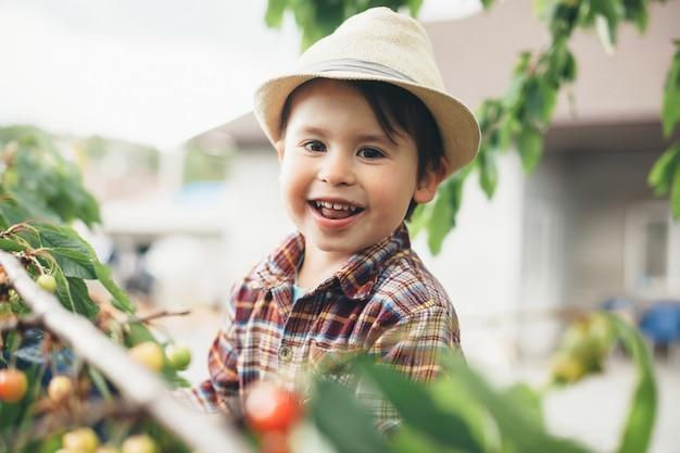 Junger kaukasischer junge, der kamera beim sitzen im baum betrachtet und kirschen isst