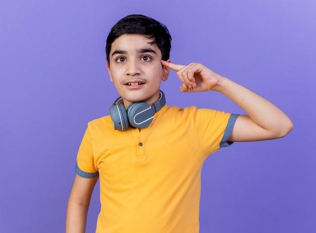Junger kaukasischer junge, der kopfhörer am hals trägt, lokalisiert auf lila wand