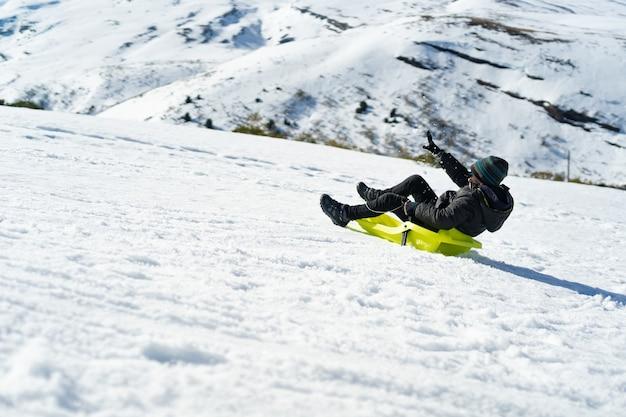 Junger kaukasischer junge, der mit einem schlitten auf dem berg spielt, der mit schnee bedeckt ist