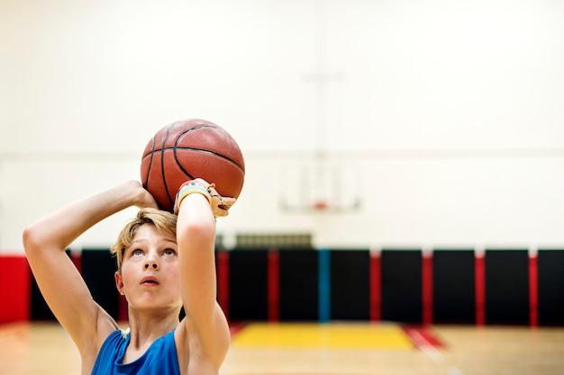 Junger kaukasischer junge, der schießenbasketball im stadion spielt