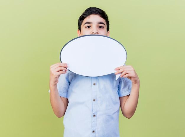 Junger kaukasischer junge, der sprachblase hält, die kamera von hinten lokalisiert auf olivgrünem hintergrund mit kopienraum betrachtet