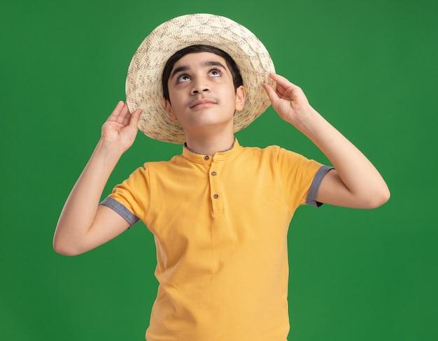 Junger kaukasischer junge, der strandhut trägt und greift, der isoliert auf grüner wand nach oben schaut