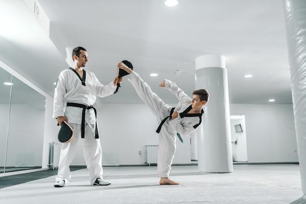 Junger kaukasischer junge im dobok, der barfuß tritt, während trainer kickziel hält. taekwondo trainingskonzept.