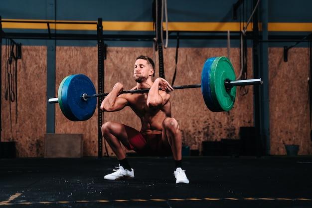 Junger kaukasischer junge in seinen 30er jahren, der das triebwerk in einem fitnessstudio anhebt?