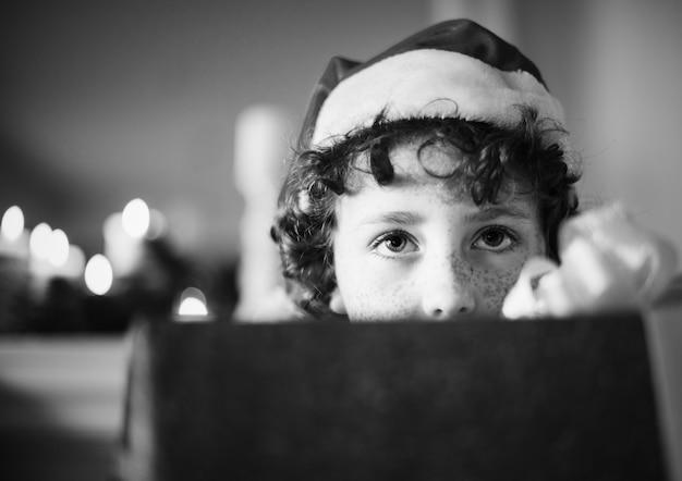 Junger kaukasischer junge mit weihnachtsgeschenkkasten