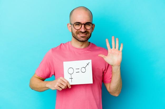 Junger kaukasischer kahler mann, der ein gleichheitsgeschlechtsplakat lokalisiert auf gelber wand hält, die fröhlich zeigt, nummer fünf mit den fingern zeigend.