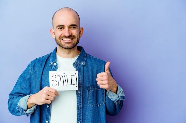 Junger kaukasischer kahler mann, der ein lächelnplakat lokalisiert hält