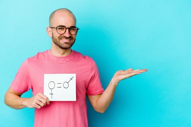 Junger kaukasischer kahlköpfiger mann, der ein gleichheitsgeschlechtsplakat lokalisiert auf gelber wand hält, die einen kopienraum auf einer handfläche zeigt und eine andere hand auf taille hält